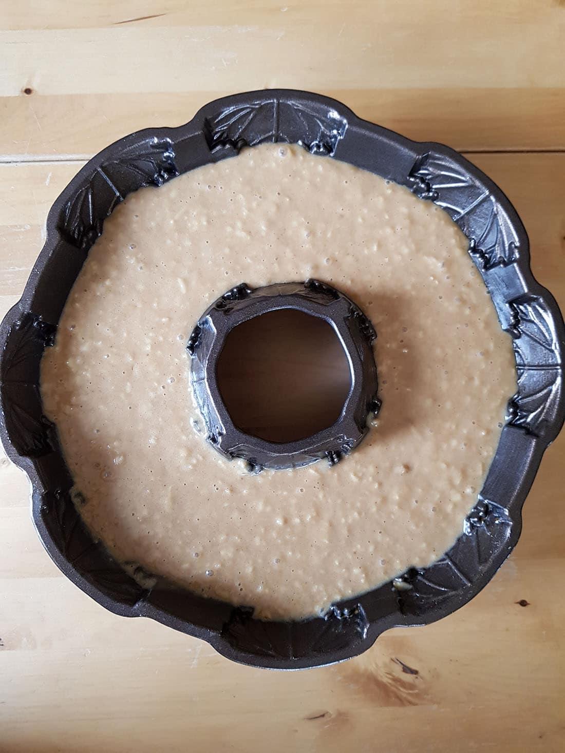A close up of glazed apple bundt cake batter in a bundt pan