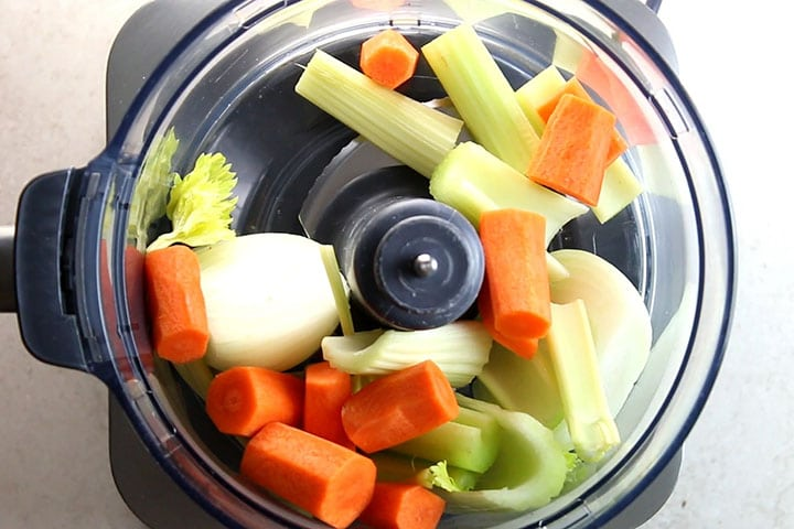 The onion carrot and celery in a food processor ready to chop