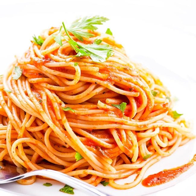 Plate of pasta with Easy Homemade Tomato Sauce and parsley sprinkled over it.