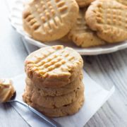 A stack of Classic Peanut Butter Cookies with a spoonful of peanut butter next to it