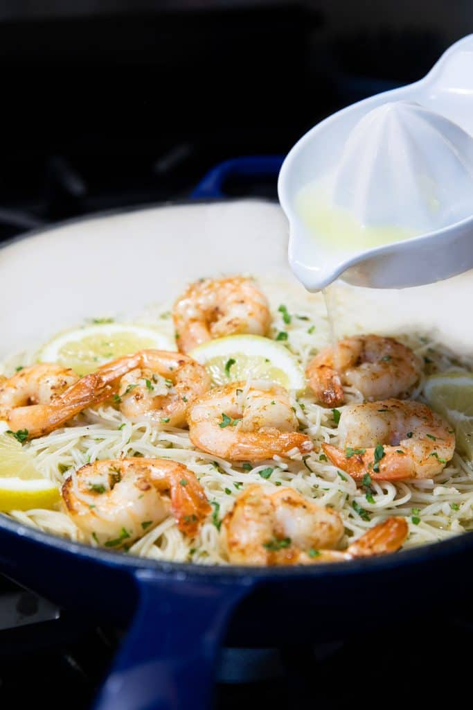 lemon juice being added to the pan with the pasta and shrimp mixture