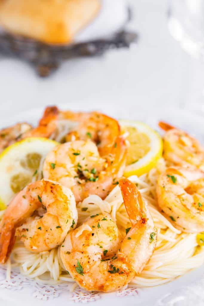 A plate full of shrimp scampi and spaghetti sprinkled with fresh chopped parsley