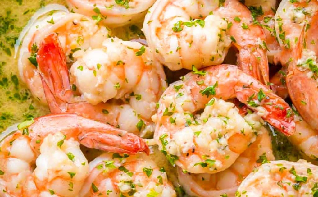 A pan with the shrimp cooking in the scampi sauce