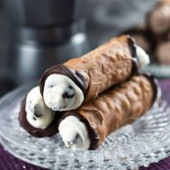 A close up of three cannoli with the ends dipped in dark chocolate with the creamy filling and chocolate chips bulging out of them