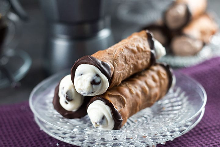 A close up of three Homemade Cannoli with the ends dipped in dark chocolate with the creamy filling and chocolate chips bulging out of them