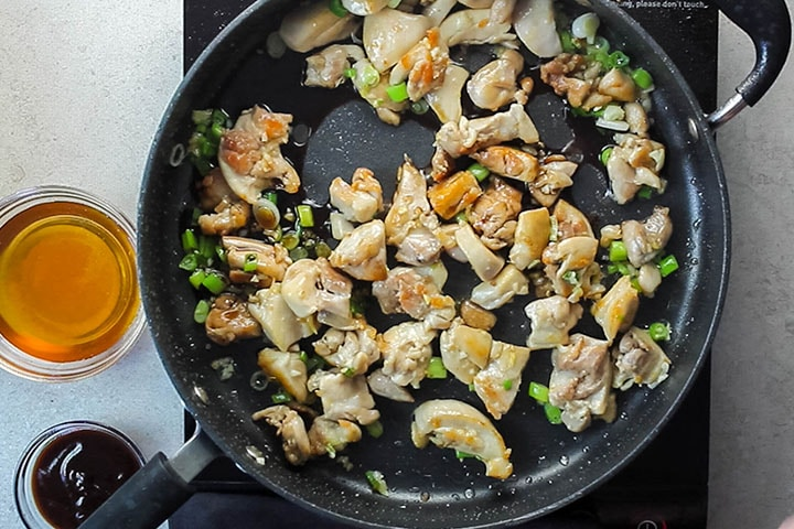 The chicken added to the onions, garlic and green onions in a wok stir frying in oil