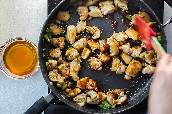 Hoisin sauce added to the pan with the chicken, garlic, ginger and green onions