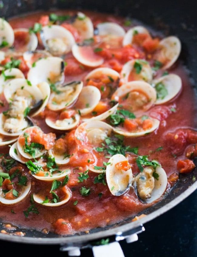 A close up of Red Clam Sauce in the pan with the clams open