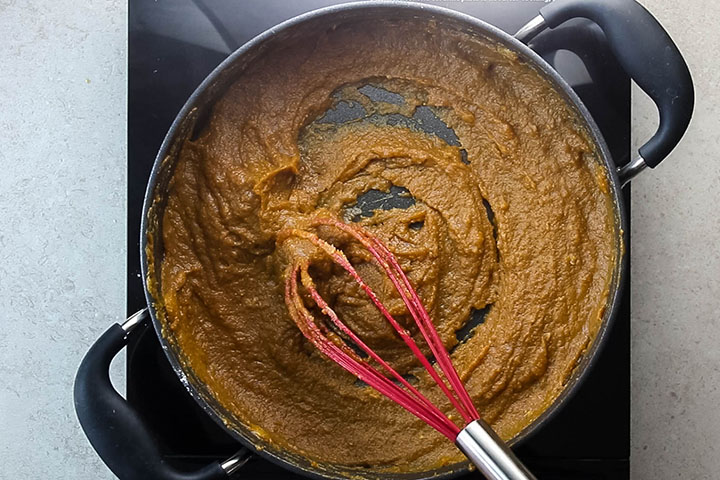 The cooked pumpkin filling in the pan with a whisk