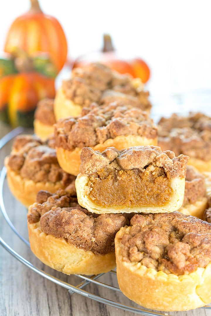 Pumpkin Streusel Tarts stacked on a cooling rack with one cut open to show the filling