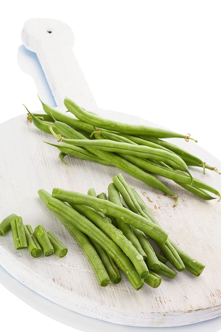 fresh green beans on a chopping board with some trimmed on the ends