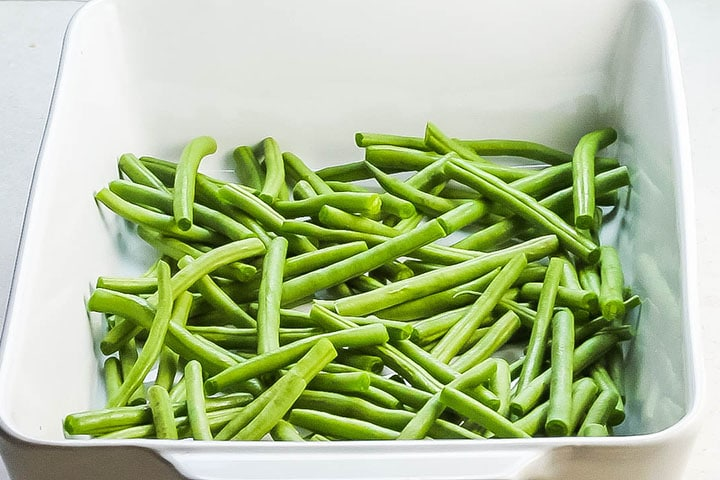 Trimmed green beans in a white roasting pan