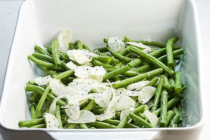 Garlic olive oil and seasoning added to the green beans in a pan