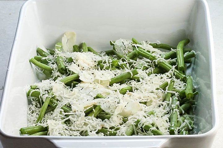 Parmesan cheese added to the Garlic olive oil and seasoning added to the green beans in a pan