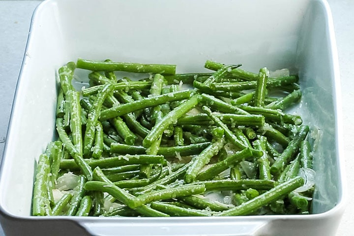 All of the ingredients tossed with the green beans in the pan