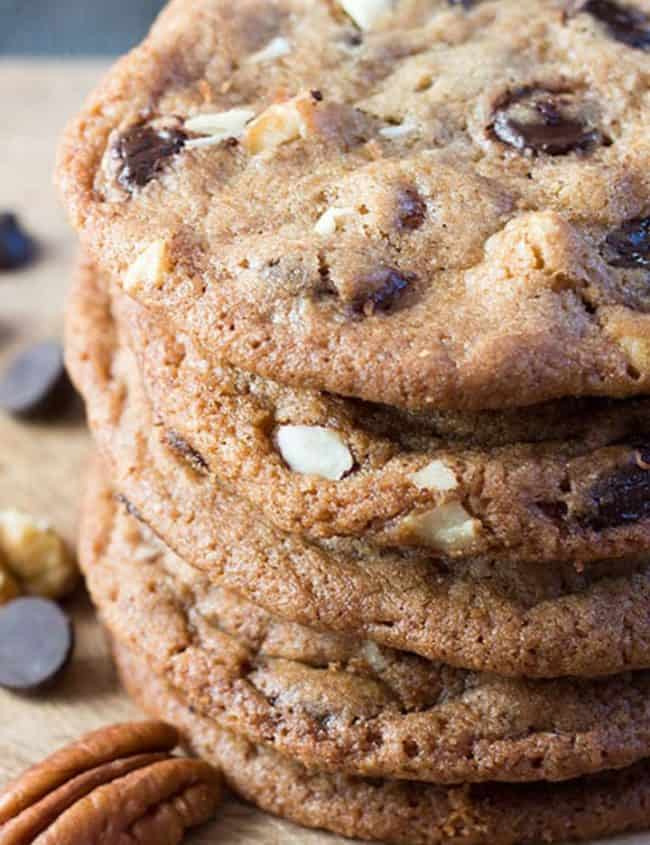 A close up of a pile of nutty chocolate chip cookies