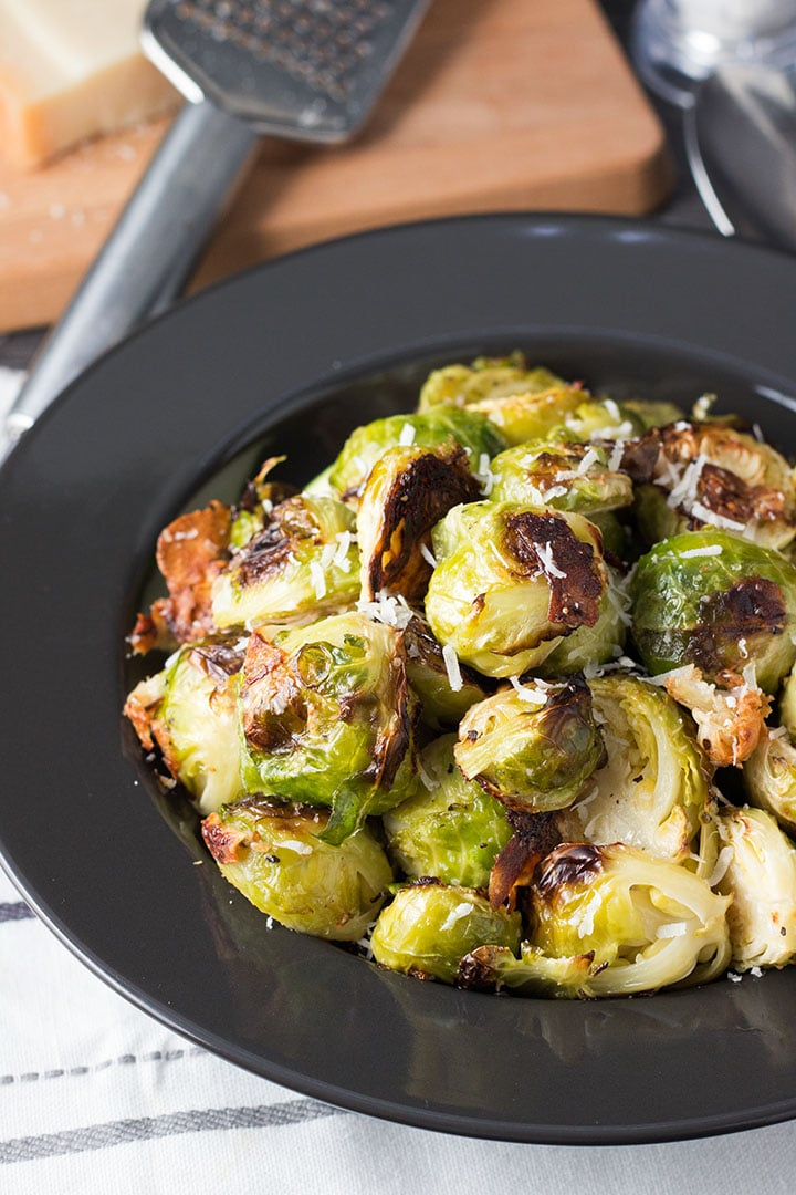 A plate of the roasted Brussels Sprouts golden and caramelized. they'll be The Best Brussels Sprouts of Your Life!