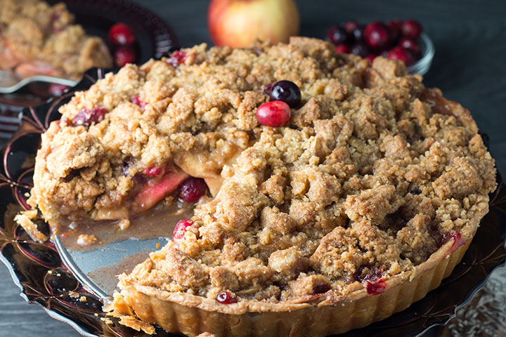 apple cranberry crumb pie with a piece cut out of it showing the fruit filling