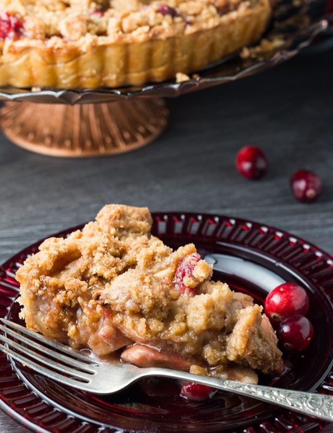 A slice of apple cranberry crumb pie on a red glass plate with a fork next to it