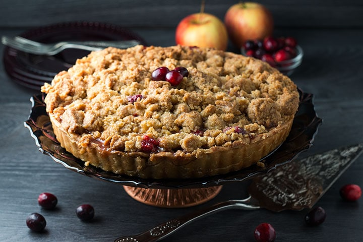 An apple cranberry crumb pie on a pie stand with cranberries on top, scattered on the table and some apples in the background.