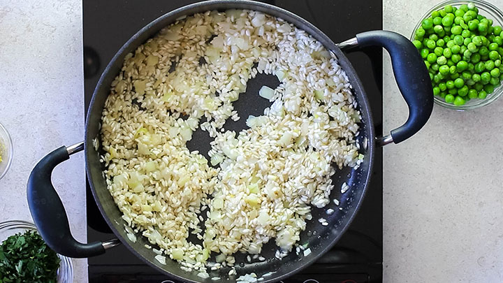 The rice in the pan with the cooked onions, celery and garlic