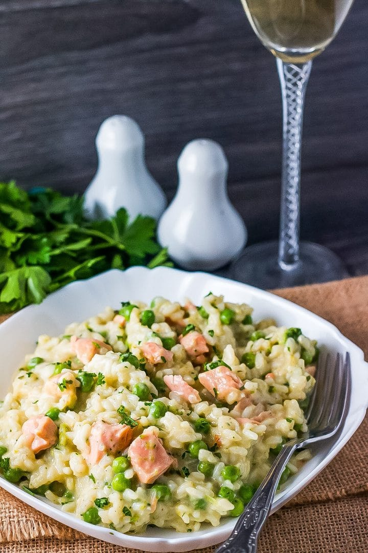 A bowl of salmon pea risotto with a fork and stem of a wine glass, salt and pepper shakers, and fresh herbs in the background