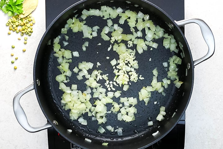 Chopped onions and thin sliced garlic sauteing in olive oil