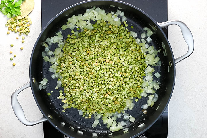 The split peas added to the pan with the onions and garlic