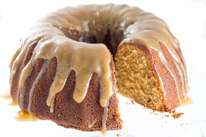 Brown Sugar Bundt Cake on a glass plate with a thicker with Caramel icing