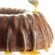 A Brown Sugar Bundt Cake on a glass cake stand being drizzled with Caramel Glaze