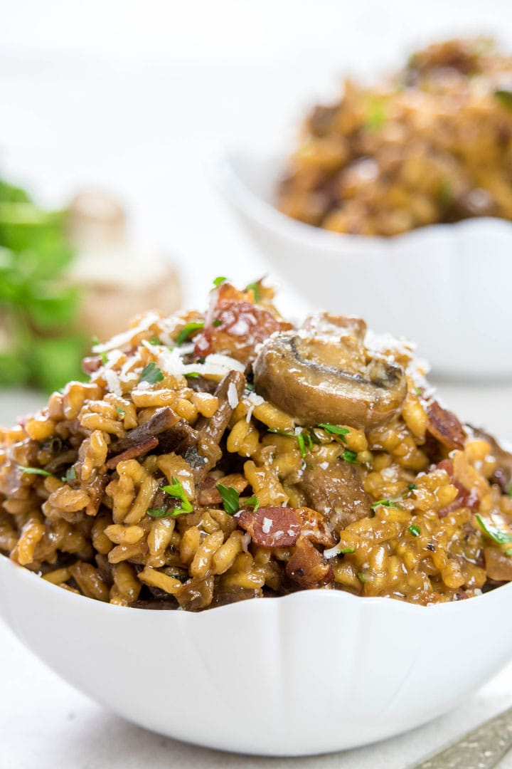 Two Bowls of Easy Mushroom & Bacon Risotto sprinkled with grated cheese and parsley