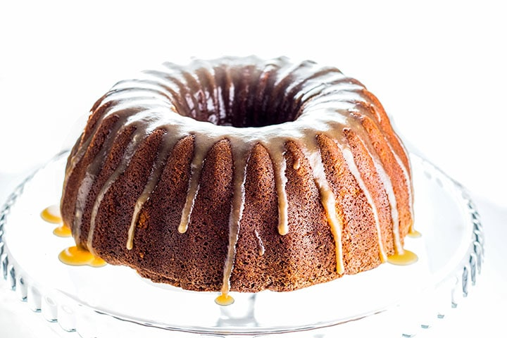 A Brown Sugar Bundt Cake on a glass cake stand dripping with Caramel Glaze