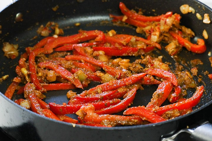 The curry paste added to the pan with the pepper mixture