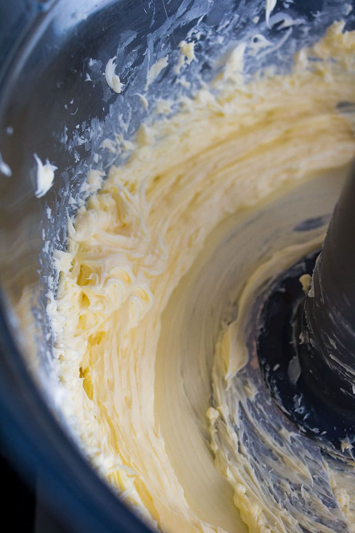 A food processor bowl with creamed butter and sugar