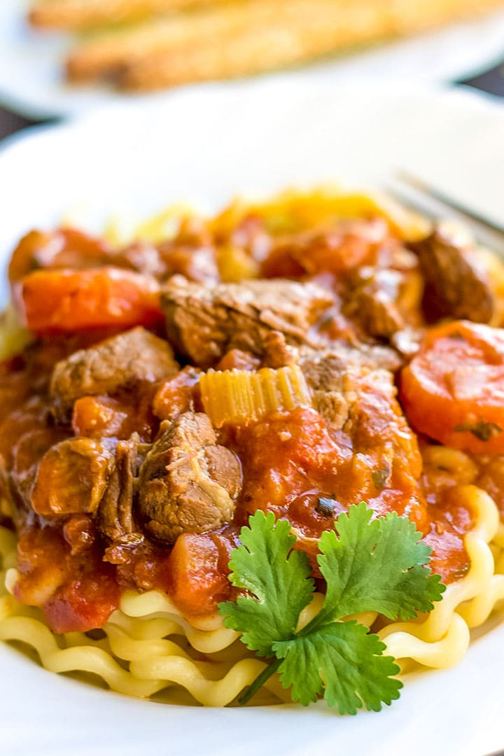 Italian Lamb stew in a plate on a bed of pasta