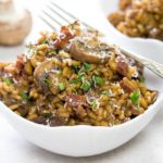 Easy Mushroom & Bacon Risotto in a white bowl scattered with fresh herbs