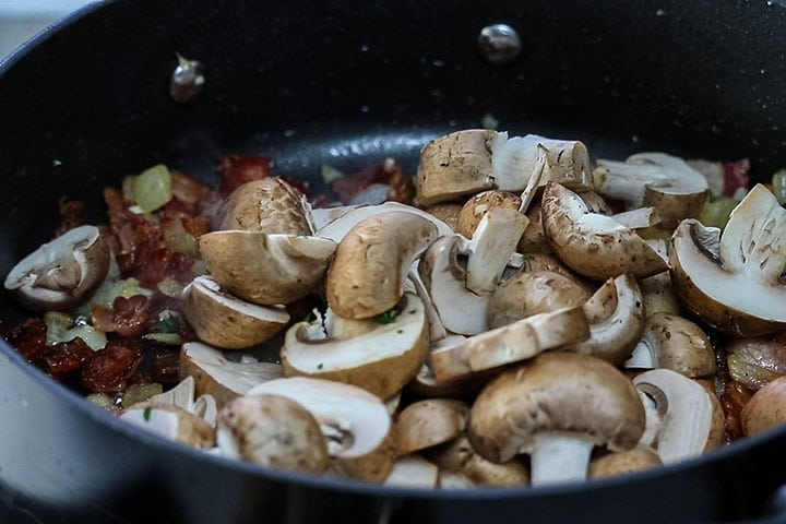 The mushrooms added to the pan with the bacon mixture.