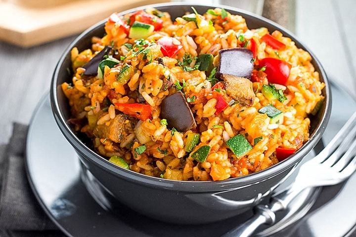 A bowl of Italian Style Rice bursting with roasted vegetables ready to eat