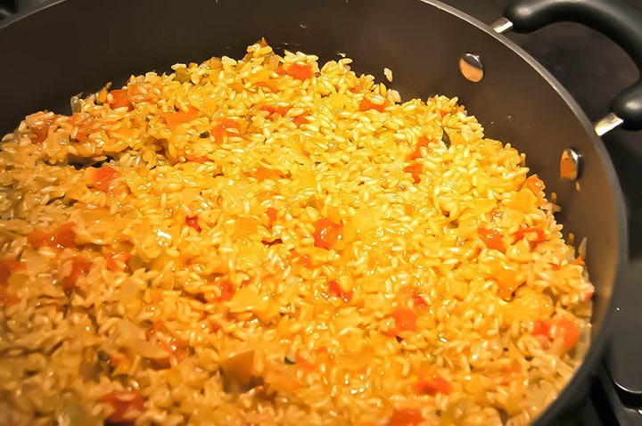 A pan with the cooked rice ready for adding the roasted vegetables