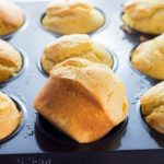 A pan of Easy Homemade Corn Muffins with one out to show the golden exterior