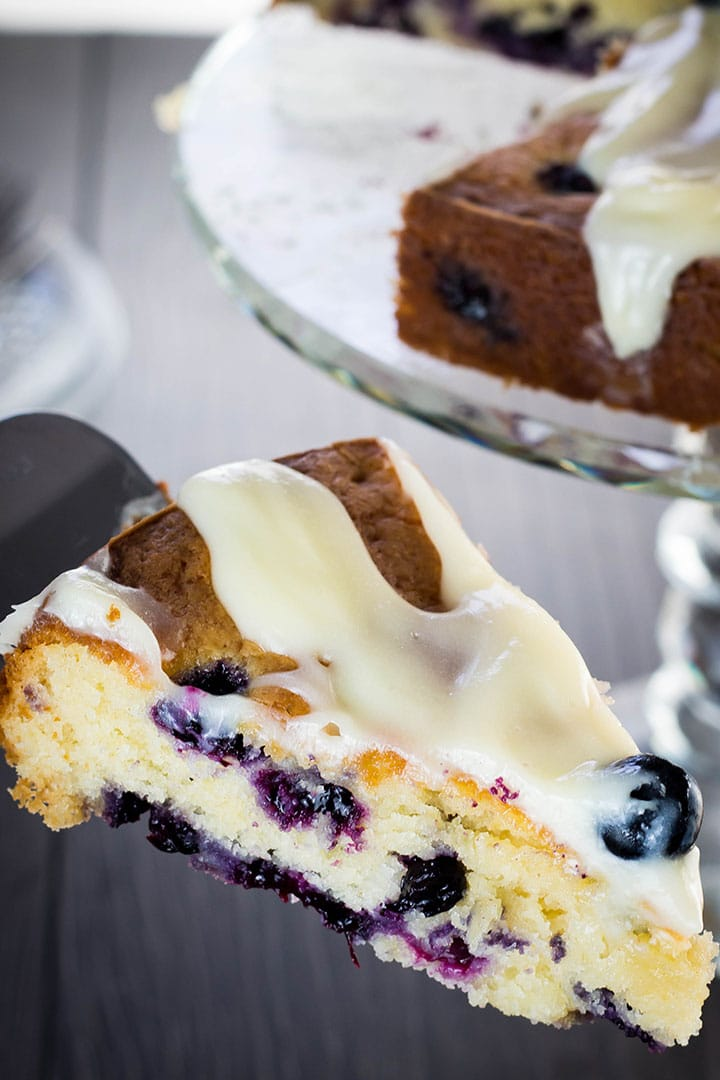 A piece of the Best blueberry cake EVER being cut from the cake