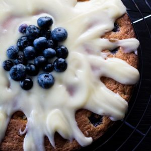 Blueberry cake drizzled with cream cheese icing and topped with some fresh blueberries