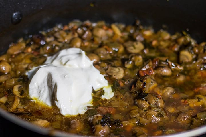 A pan with mushrooms cooking with a dollop of sour cream
