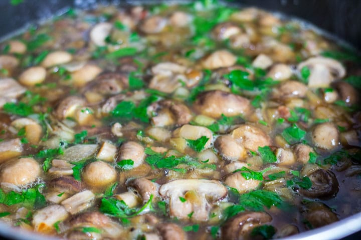 The white wine, stock and parsley added to the pan