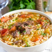 a big bowl full of Slow Cooker Oxtail Orzo Soup sprinkled with fresh parsley