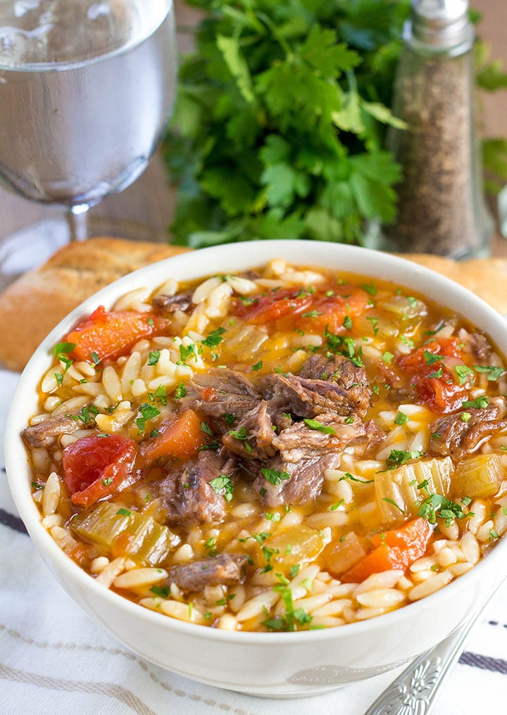 a bowl of slow cooker oxtail orzo soup with fresh herbs in the background