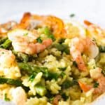 A slose up photo of a plate piled high with yellow rice, asparagu and plump shrimp