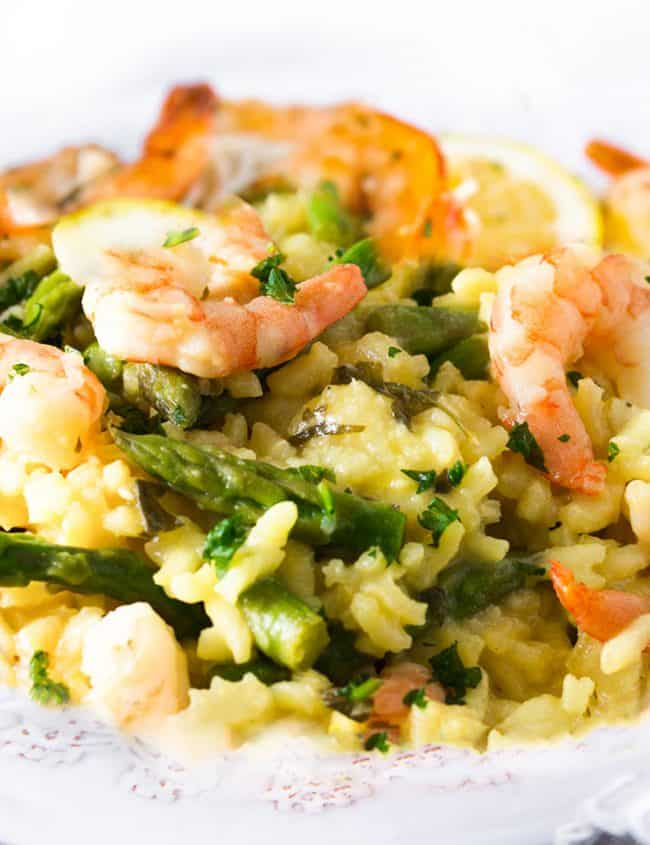 A dish piled high with yellow rice, asparagu and plump shrimp