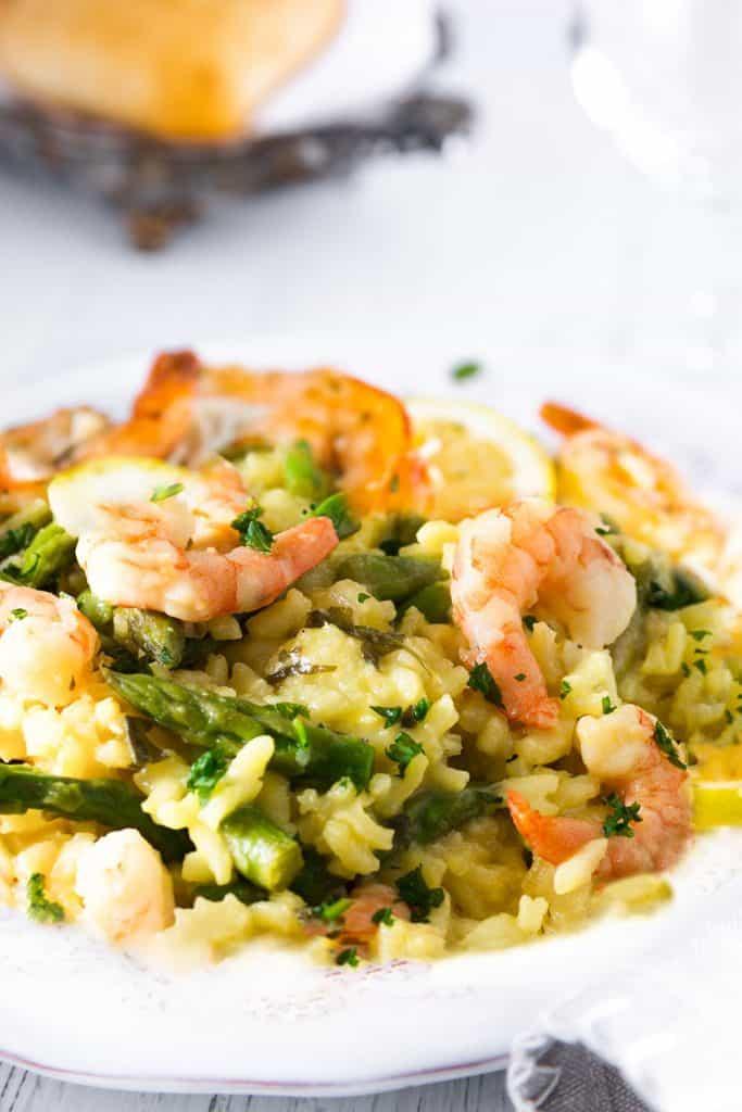 A dish piled high with yellow rice, asparagu and plump shrimp