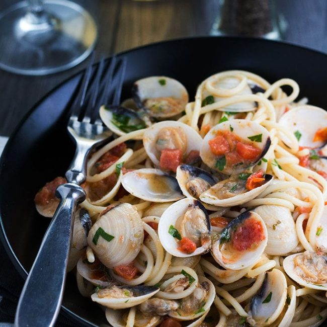 Spaghetti with Clam Sauce served on a pplate with the clams still in their shells and a fork next to the dish